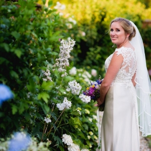 Bride poses in the walled garden next to the flowers