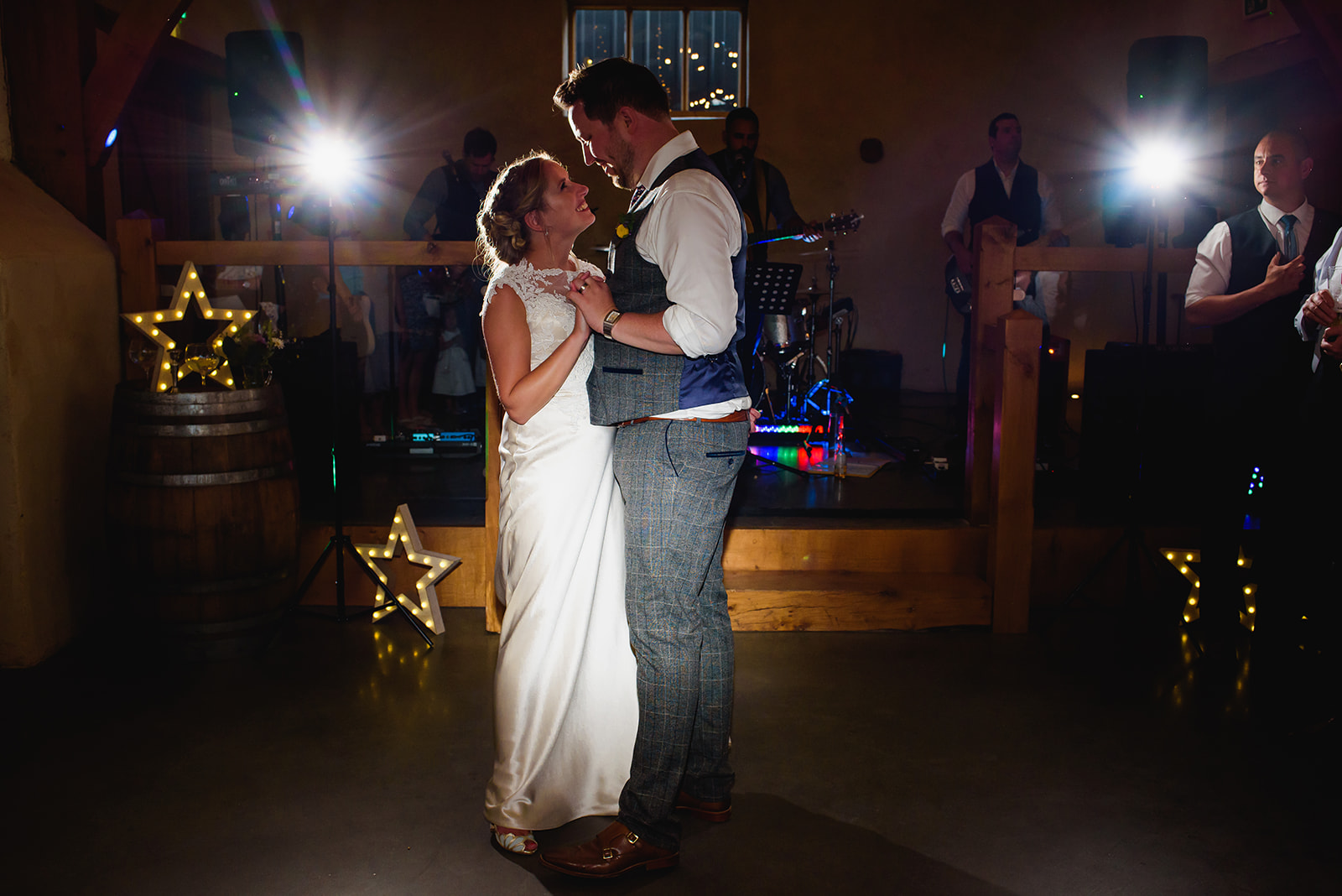 Bride and groom take their first dance in front of the band in the Cider Barn