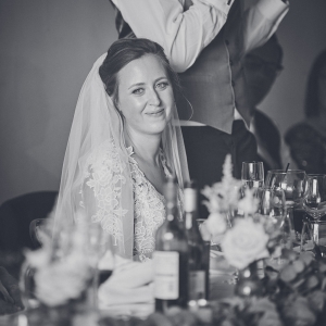 Bride smiles as her husband delivers his speech