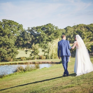 Bride and groom walk besides the lake at Upton Barn & Walled Garden
