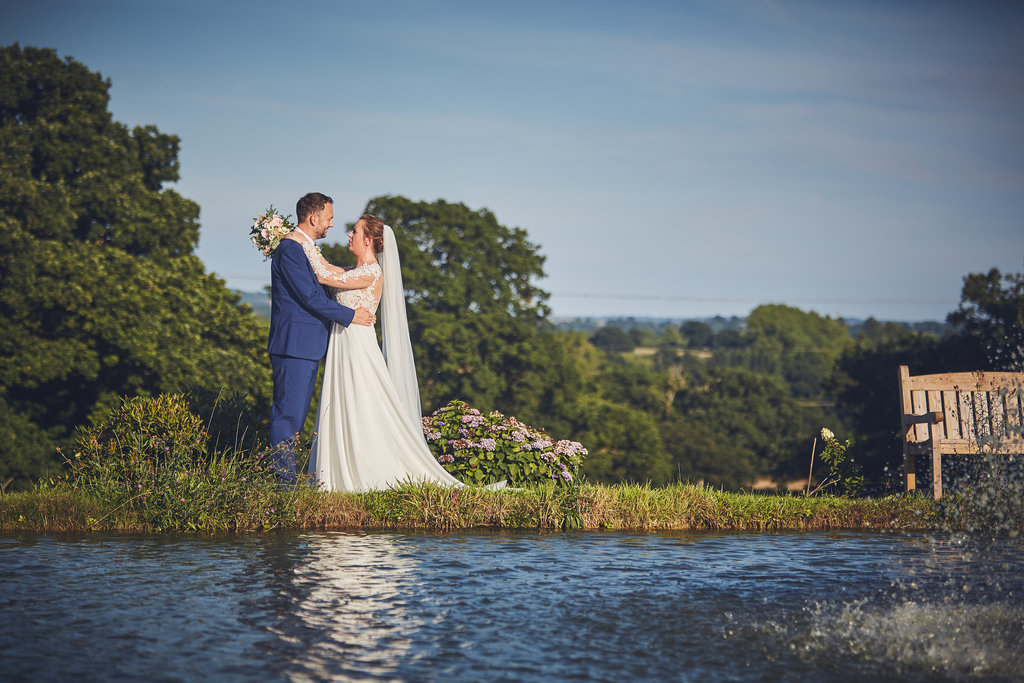 Bride and groom embrace besides the lake at Upton Barn & Walled Garden