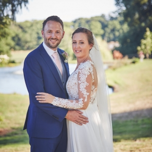 Bride and groom embrace in front of the lake at Upton Barn & Walled Garden