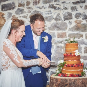 Bride and groom cut their wedding cake in the barn