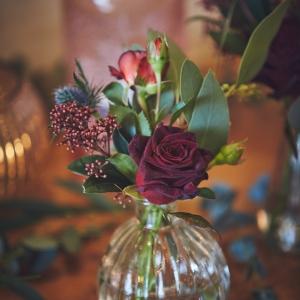 Close up of deep red roses in vintage bud vase