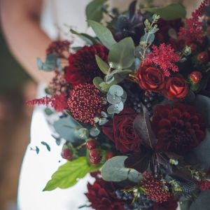 Close up of deep red bridal boquet with roses and eucalptus