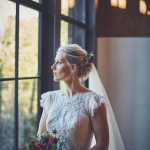 Bride holds deep red bouquet by large window at The Stables Barn at Upton