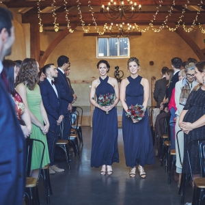 Bridesmiads in deep blue walking down the aisle in Upton Barns Cider Barn Wedding Ceremony