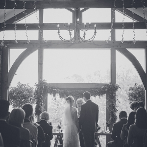 Black and white photo of couple from the back exchanging vows in civil ceremony in Uptons Cider Barn