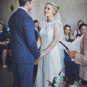 Bride and groom exchange vows facing each other in the Cider Barn at Upton Barn