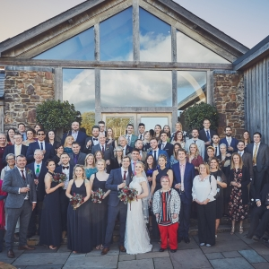 Group wedding photo on the steps of the Cider Barn at Upton