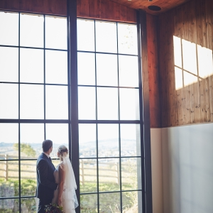 Bride and groom embrace by the large window of the Stable Barn at Upton and enjoy the view.