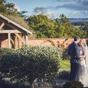 Bride and groom embrace in picturesque walled garden with Blackdown Hills in the distance
