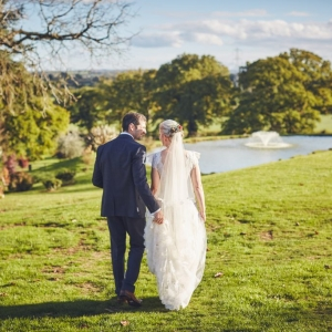 Bride and Groom walk towards the lake and fountain at Upton