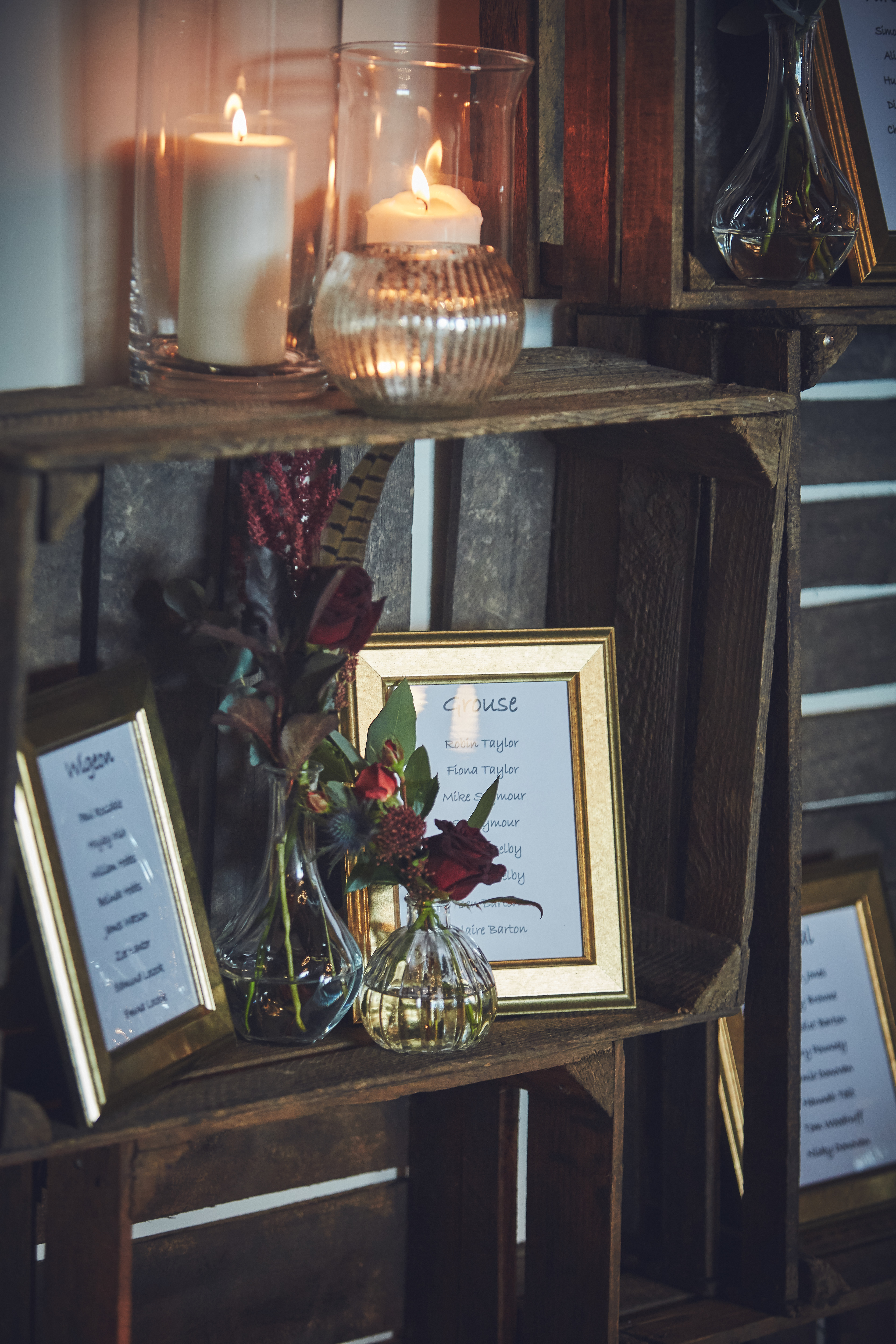 Wedding table plan stacked up in dark crates with seating plan displayed in gold frames