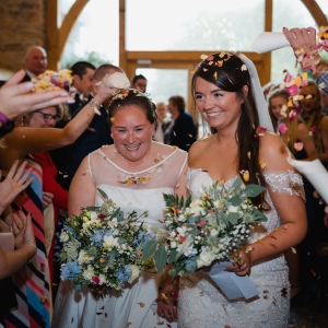 Brides smiling under arch of confetti in the Cider Barn at Upton