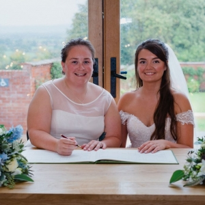 Newly wed brides sign the register at Upton Barn Civil Ceremony