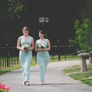 Bridesmaids in green dresses clutching bouquets walk down the drive at Upton Barn