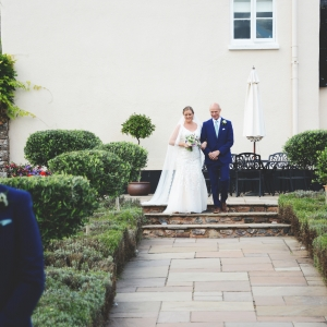Bride and her father descend the steps in the Walled Garden at Upton