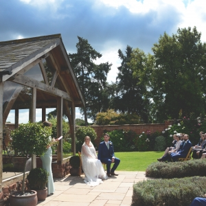 Guest gives a reading to the wedding congregation by the Arbor in the Walled Garden at Upton Barn