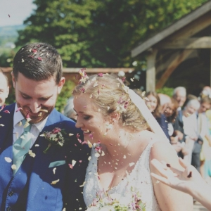 Bride and groom are showered with petal confetti in the Walled Garden at Upton Barn