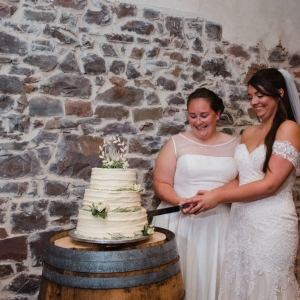 Brides cutting their wedding cake at civil ceremony at Upton Barn & Walled Garden wedding venue in Devon