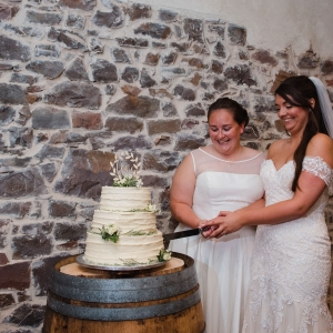 Brides cutting their wedding cake at civil ceremony at Upton Barn & Walled Garden wedding venue in Devon