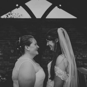 Smiling brides share look into each others eyes in the Arbor at Upton Barn