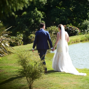 Bride and groom walk around the lake hand in hand at Upton Barn
