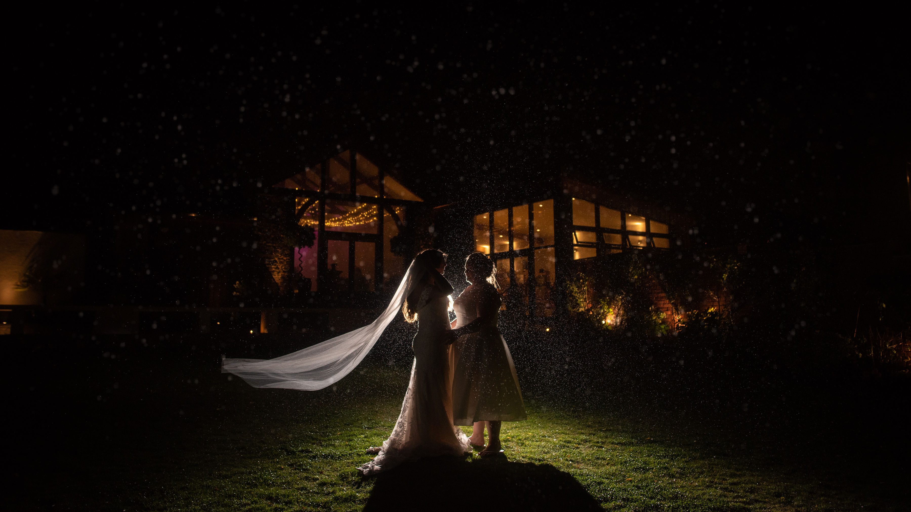 Brides silhouetted by light and rain in front of the Barn at Upton