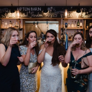 Bride takes a drink with guests in The Press Bar at Upton barn