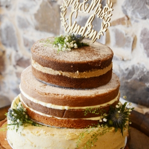 Naked wedding cake with the married couples name upon the top