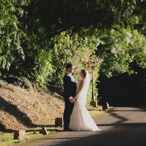 Married couple hold hands in low sun in the lane at Upton Barn