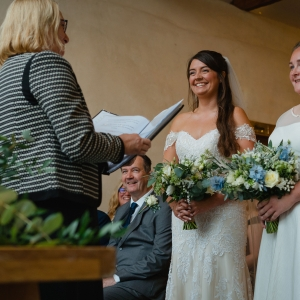 """Smiling brides say """"I do"""" in a civil ceremoney inside Upton Barns Cider Barn"""