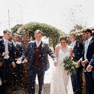 Bride and Groom engulfed in confetti by the gate to the Walled Garden at Upton Barn