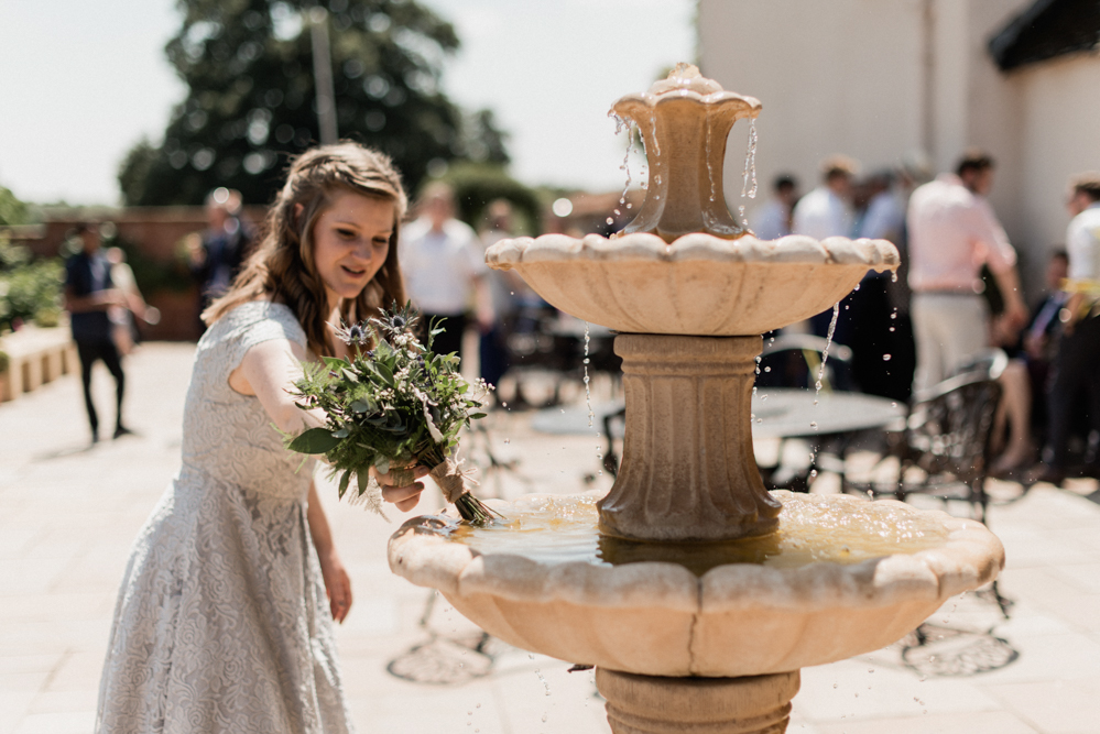Bridesmaid gives her bouquet a drink from the fountain at Upton during one of the hottest summers