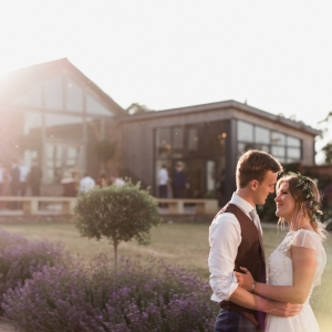 Bride and groom embrace in front of the Cider Barn and the Press Bar at Upton