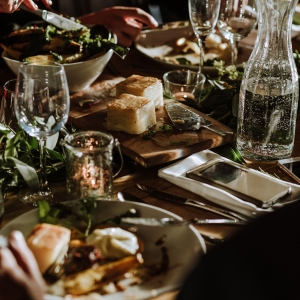 Close ups of sumptuous plates of food  and carafes of water on wooden table