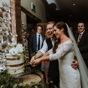 Bride and Groom joyfully cut wedding cake surrounded by guests by stone wall in the Cider Barn