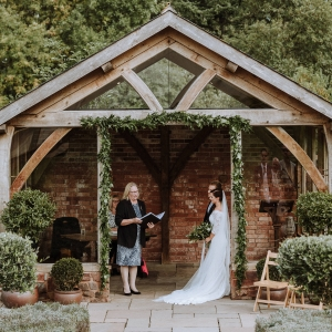 Registar conducts the civil wedding at Upton Barn in the Arbor with Bride and Groom
