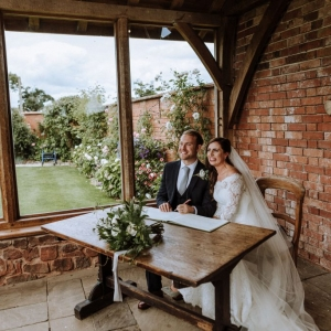 Bride and Groom beam smiles seated at the table in the Arbor after signing the register at Upton Barn