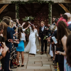 Bride and Groom in a flurry of confetti by the Arbor at Upton Barn