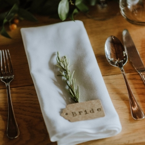 Place setting with rosemary on a wooden table with a white napkin at Upton Barn