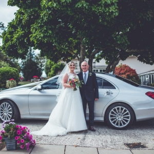 Bride and her father stand by their chauffered car
