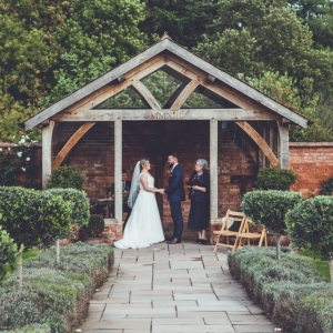 Bride and Groom exchange vows in the Arbor at Upton Barn