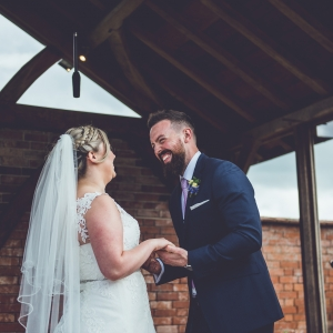 Bride and groom laughing under the microphone in the Arbor at Upton Barn