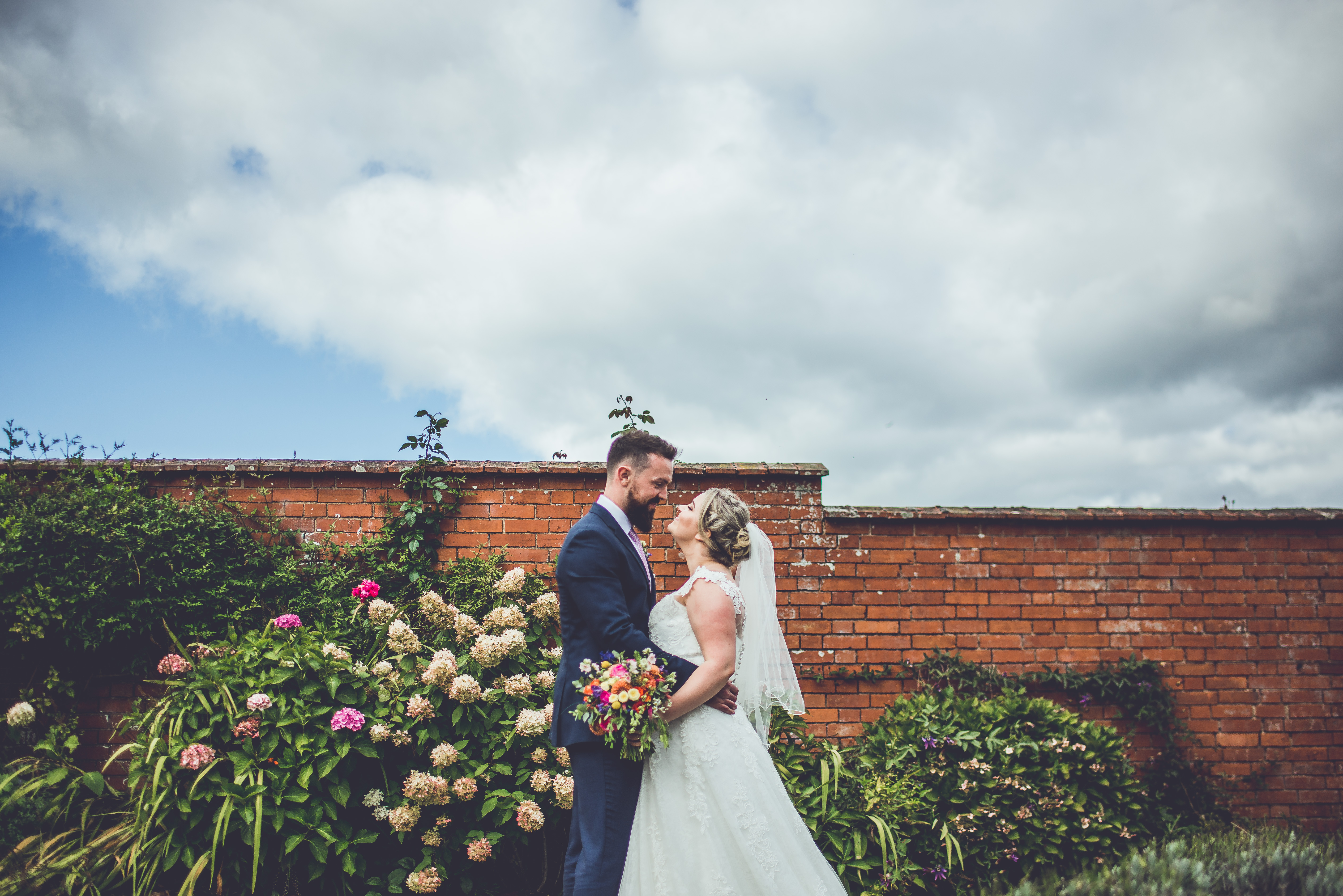 Bride and Groom look into each others eyesin an embrace by the Walled Garden at Upton Barn
