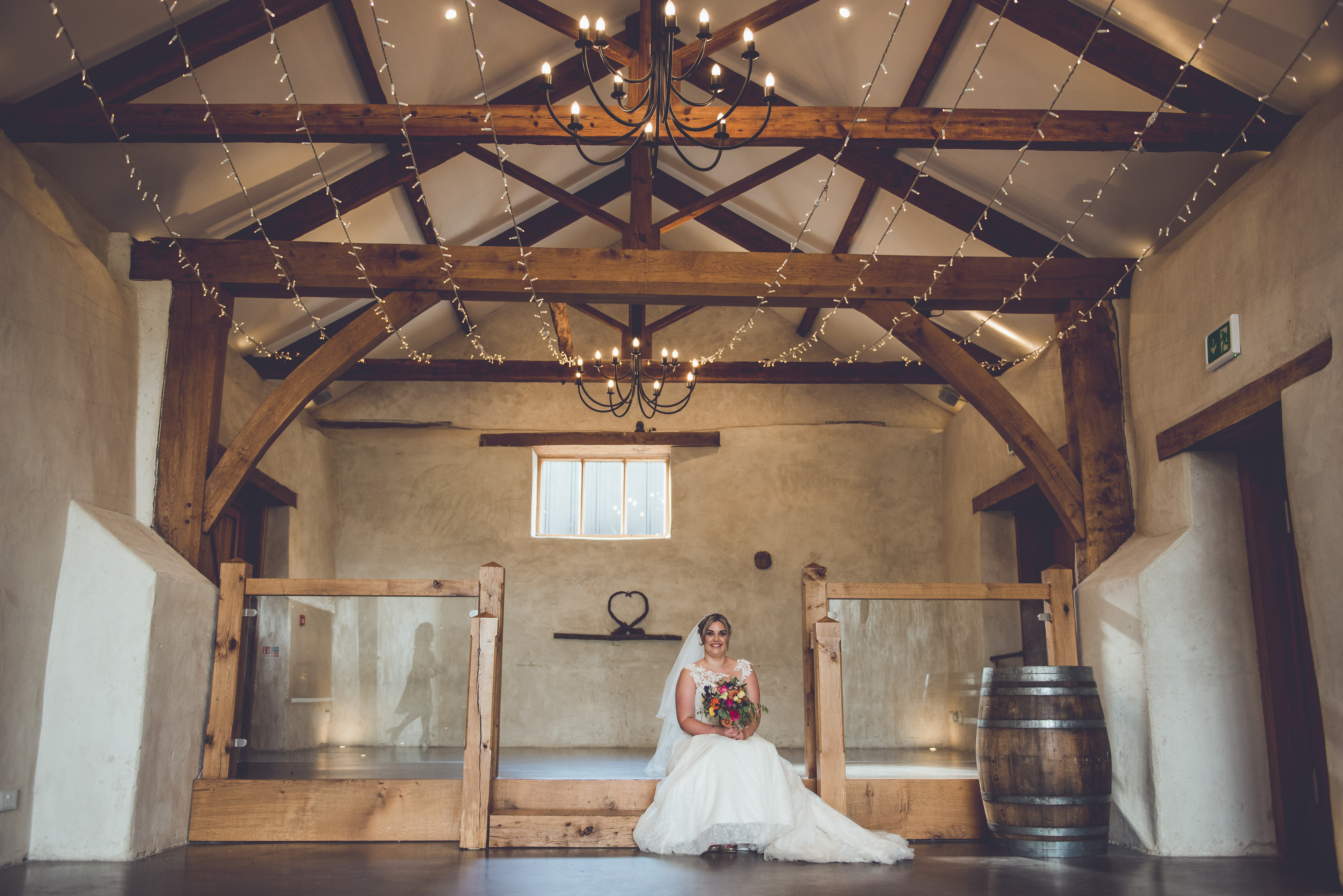 Bride holding bouquet seated on the steps inside the Cider Barn at Upton Barn