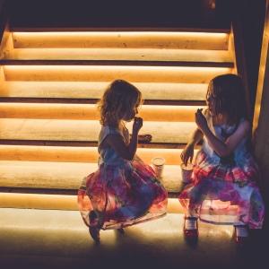 Flowers girls enjoying a snack on the lit Press Bar steps at night