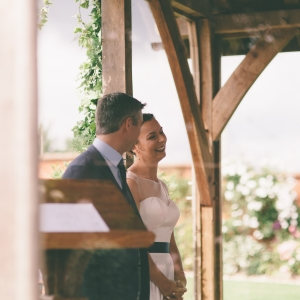 Bride smiles with ease as the couple exchange wedding vows in the Arbor at Upton Barn