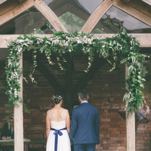 Bride and Groom exchange wedding vows in the Arbor at Upton Barn